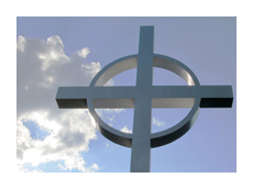 Cross backlit by sky and clouds